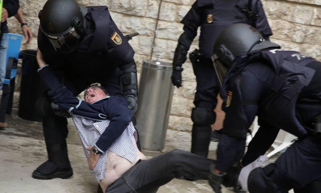 Home é arrastado por policiais durante os embates em Barcelona Foto: STRINGER / REUTERS