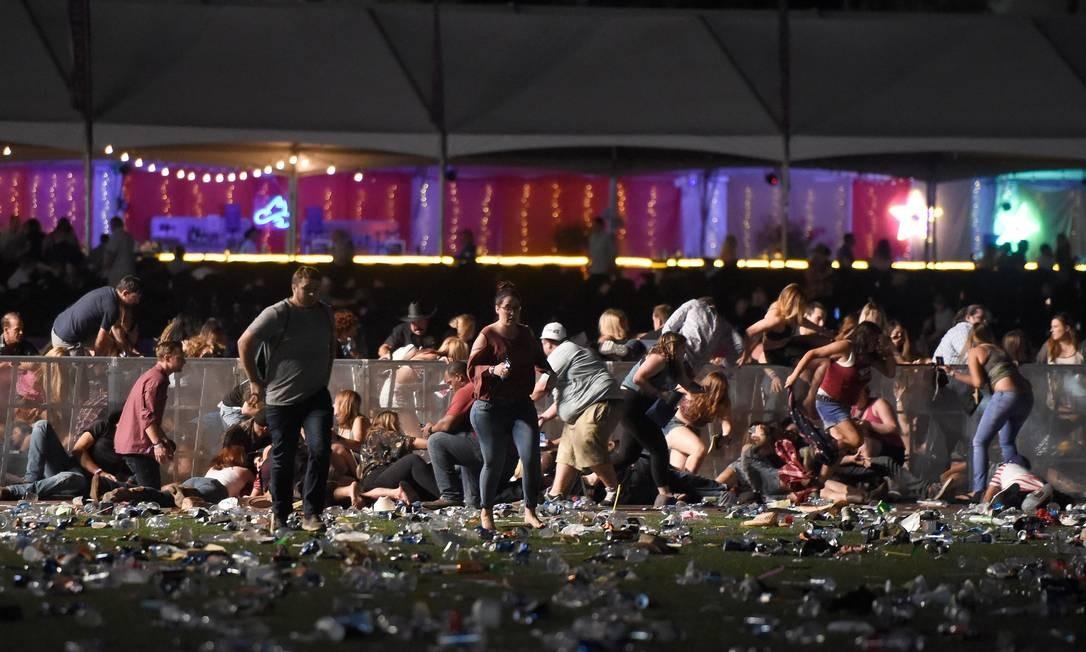 Pessoas correm após ouvirem disparos no Mandalay Bay Resort e Casino Foto: David Becker / AFP