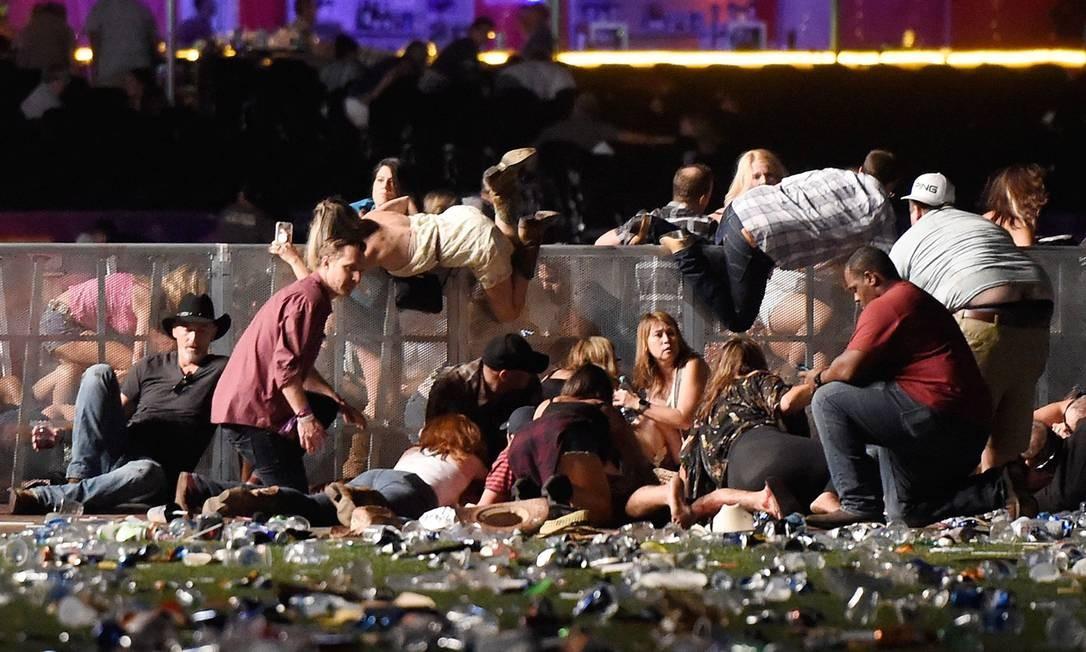 Pessoas procuram por abrigo durante o ataque armado em um festival de música country em Las Vegas, nos EUA Foto: David Becker / AFP