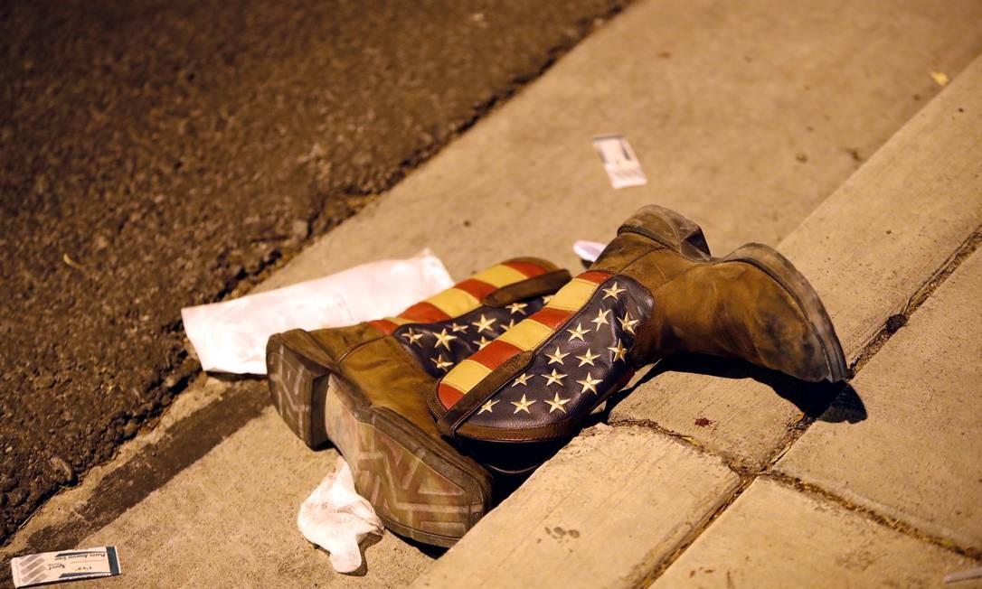 Um par de botas de cowboy é largado no meio da calçada Foto: Steve Marcus / Reuters