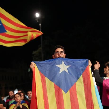 Homem segura uma bandeira separatista catalã na Praça da Catalunha após o fim da votação do referendo em Barcelona Foto: SUSANA VERA / REUTERS