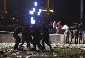 Pessoas ajudam ferido após tiros em Las Vegas Foto: David Becker / AFP