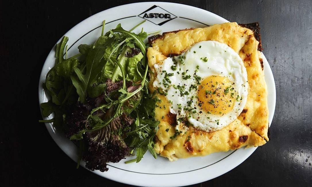 O Astor aposta no croque monsieur (R$ 38), feito com presunto e queijo gruyère, gratinado com molho béchamel e mais queijo, que chega à mesa com salada verde, e o croque madame (na foto, R$ 40), que leva um ovo frito em cima, também servido com salada verde. Astor: Av. Vieira Souto 110, Ipanema — 2523-0085. Seg a qua, das 18h à 1h. Qui, das 18h às 2h. Sex, das 13h às 3h. Sáb, do meio-dia às 3h. Dom, do meio-dia às 22h Foto: Divulgação/Bruno Geraldi