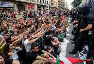 Manifestantes protestam diante de agentes que protegem a Estação da Polícia Nacional, em Barcelona Foto: YVES HERMAN / REUTERS
