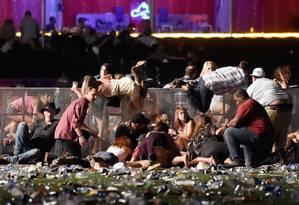 Desespero. Público de um festival de música country, no Mandalay Bay, em Las Vegas, corre para se proteger de tiros disparados do 32º andar de um hotel, por Stephen Paddock: maior atentado a tiros da história dos EUA, com 59 mortos e mais de 500 feridos Foto: David Becker 02/10/2017 / AFP