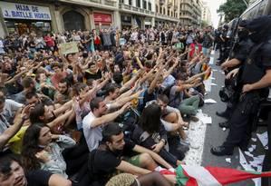 Protestos pacíficos. Sentados, manifestantes gritam palavras de ordem contra a polícia espanhola na sede da entidade, em Barcelona, em resposta à repressão à consulta sobre independência Foto: YVES HERMAN / YVES HERMAN/REUTERS