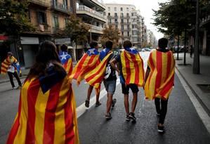 Manifestantes se enrolam em Esteladas, as bandeiras catalãs que servem de símbolo da independência Foto: JON NAZCA / REUTERS