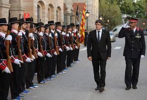 O presidente da região da Catalunha, Carles Puigdemont, e Josep Lluis Trapero (à dir.), chefe da Mossos D'Esquadra (polícia catalã), caminham em frente aos agentes antes de uma cerimônia em Barcelona Foto: LLUIS GENE / AFP