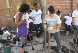 Voluntária e moradora na construção de fundação de casa Foto: Divulgação