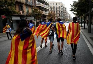 Catalães caminham por Barcelona com as bandeiras estreladas do movimento independentista Foto: JON NAZCA / REUTERS