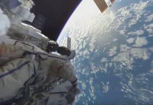 Um dos cosmonautas durante a caminha espacial, com a Terra ao fundo Foto: REPRODUÇÃO