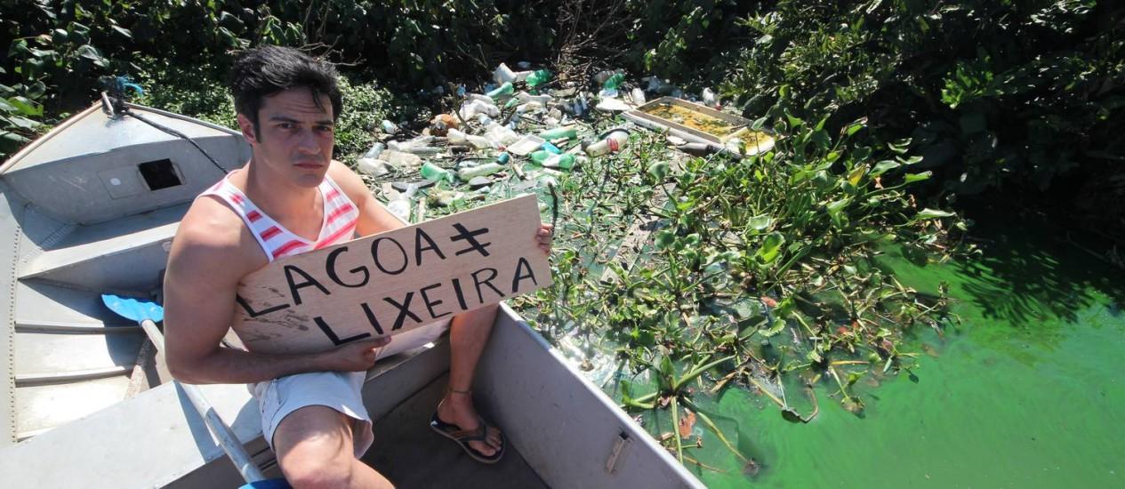 Mateus Solano segura placa com lixo espalhado ao fundo Foto: Mario Moscatelli