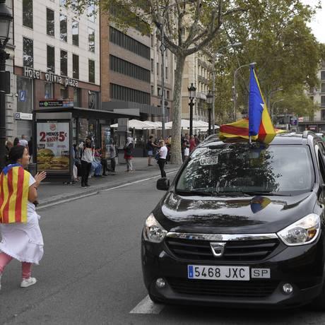 Estudantes levando a Estelada (bandeira pró-independência catalã) passam ao lado de um taxi na Praça da Catalunha durante greve geral na região Foto: LLUIS GENE / AFP
