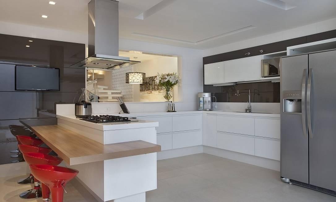 Os tons neutros também foram os escolhidos para a cozinha, com as banquetas vermelhas funcionando como ponto de cor do espaço Divulgação