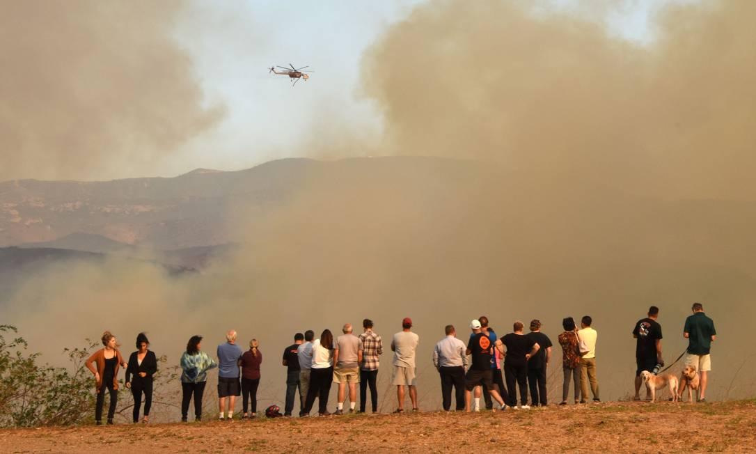 Grupo de pessoas acompanha ação de helicóptero que despeja água sobre incêndio em Orange ROBYN BECK / AFP