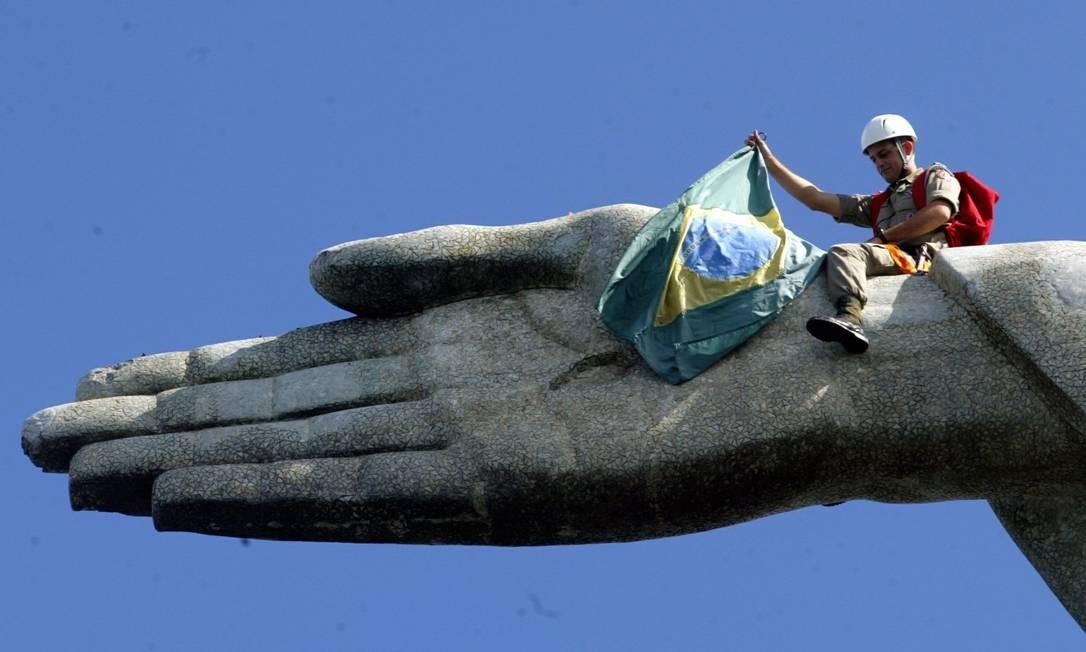 Bandeira brasileira é levada para a mão do Cristo nas comemorações pelo Dia Mundial do Meio Ambiente, em 05/06/2005 Foto: Gabriel de Paiva / Agência O Globo
