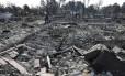Homem caminha sobre as cinzas de onde ficava a sua casa em Santa Rosa, Califórnia
