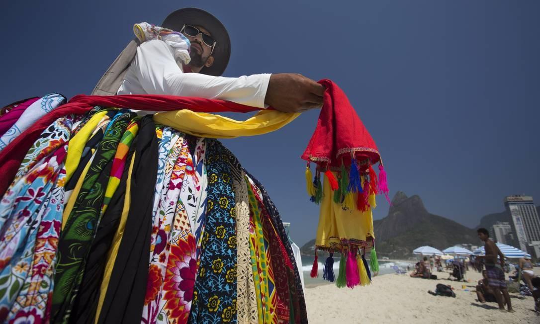 67019a0ec5f9 Colorido na areia: vendedor Luis Paulo de Souza mostra as cangas com pompom  Foto: