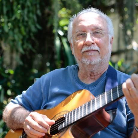 Menescal toca violão no jardim de sua casa, na Barra Foto: Brenno Carvalho / Agência O Globo
