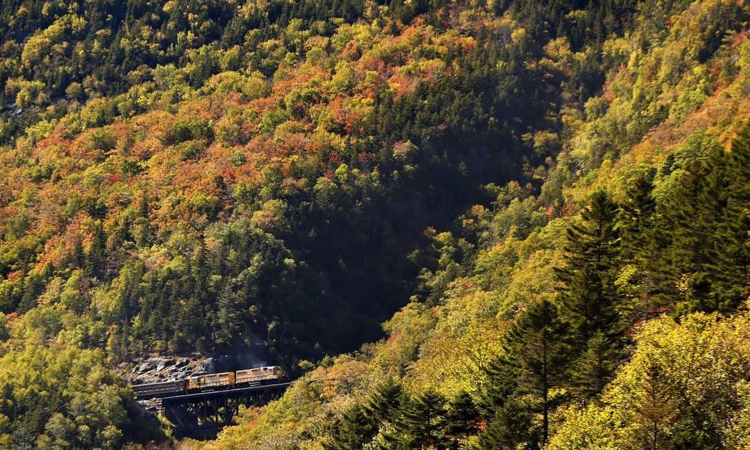 """Trem percorre a Conway Scenic Railroad, em Crawford Notch, New Hampshire. Nos Estados Unidos são comuns excursões a bordo de trens e ônibus por estradas cênicas pintadas pelas cores de outono, para observar o fenômeno da """"foliage"""", a queda das folhas Robert F. Bukaty / AP"""
