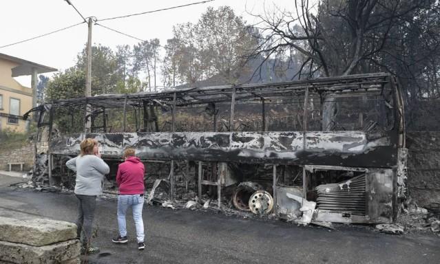 Mulheres observam destroços de ônibus, que ficou destruído após ser tomado pelas chamas em Pontevedra, na Galícia