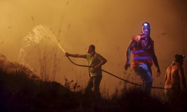 Voluntários tentam apagar fogo com mangueira; dezenas de pessoas já morreram em decorrência de incêndios em Portugal e Espanha