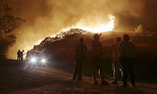 Portugueses assistem às chamas tomando conta de mata perto de casas nos arredores de Obidos, cidade popular entre turistas; incêndios florestais atingem diversos pontos de Portugal