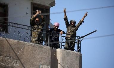 Combatentes das Forças Democráticas da Síria fazem gesto de vitória em Raqqa Foto: RODI SAID / REUTERS