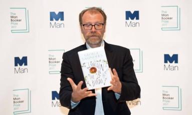 Autor americano George Saunders com a capa de seu livro Foto: CHRIS J RATCLIFFE / AFP