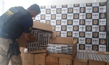 Agente empilha caixas onde estão armazenados os maços de cigarros Foto: Divulgação/PRF