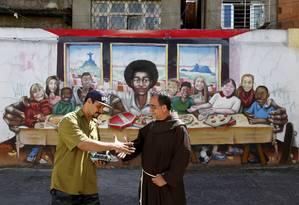 Frei Sandro e o grafiteiro Acme se cumprimentam diante de sua obra, o painel da Santa Ceia com pizza e Jesus Negro feito em parede da Igreja Nossa Senhora da Boa Viagem, na Rocinha Foto: Agência Globo / Pablo Jacob
