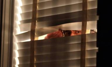 Um homem olha pela janela da casa de Aécio Neves: senador nega que seja ele na imagem Foto: Luis Nova/Esp. CB / Agência O Globo