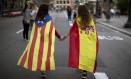 Meninas carregam nas costas bandeiras da independência da Catalunha e da Espanha em um protesto em Barcelona Foto: Emilio Morenatti / AP