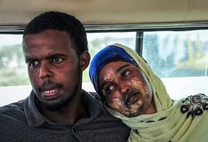 Vítima gravemente ferida no atentado na Somália espera uma ambulância, ao lado do marido, antes de ser encaminhada ao aeroporto internacional Aden Adde, para receber atendimento médico Foto: MOHAMED ABDIWAHAB / AFP