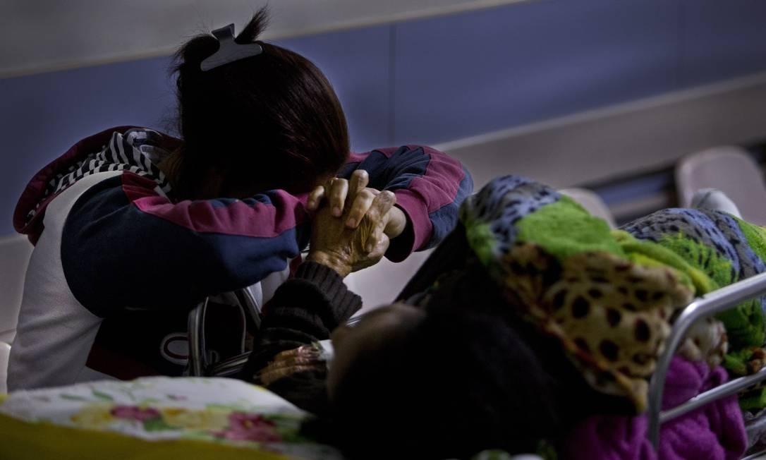 Acompanhante segura a mão de paciente à espera de atendimento em corredor do Hospital Salgado Filho em 17/10/2017 Foto: Antonio Scorza / Agência O Globo