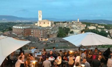 Bela vista. Turistas lotam restaurante em encosta de Perugia, capital da Úmbria Foto: Albert Stumm / AP
