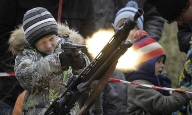 Menino usa arma da Segunda Guerra com munição de festim em exposição em show militar em São Petersburgo, Rússia: Exército apela para memória saudosista da população às vésperas do aniversário da Revolução Russa Foto: Dmitri Lovetsky/14-10-2017 / AP