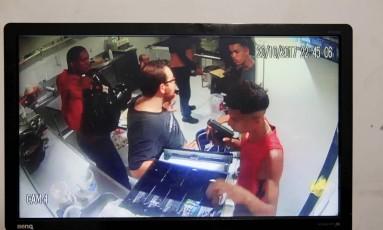 Câmeras capturaram ação de bandidos. Na imagem, homem de vermelho segura uma arma, após bando render funcinários Foto: Uanderson Fernandes / Agência O Globo