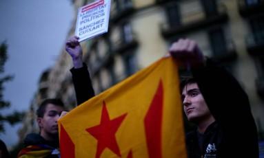 """Um manifestante segura a bandeira símbolo da Catalunha separatista enquanto outro, ao lado, levanta um pequeno cartaz no qual se lê """"Liberdade presos políticos, Sanchez Cuixart"""", referindo-se aos dois maiores líderes de organizações separatistas da região, Jordi Sanchez and Jordi Cuixart Foto: IVAN ALVARADO / REUTERS/19.10.2017"""