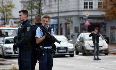 Policiais montam guarda em um dos locais onde o agressor esfaqueou pessoas, na praça Rosenheimer Foto: CHRISTOF STACHE / AFP