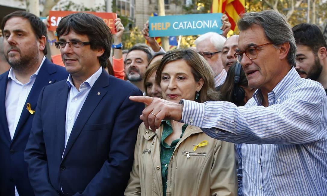 O ex-presidente do governo regional catalão, Artur Mas (à direita), junto ao atual Carles Puigdemont (de óculos e terno azul), e o vice-presidente regional Oriol Junqueras durante passeata pelas ruas de Barcelona Foto: Manu Fernandez / AP