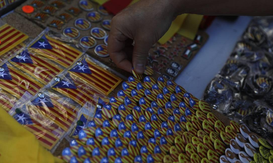 Um homem pendura botons que com a bandeira da Catalunha, imagem que simboliza e reforça a independência local Foto: Santi Palacios / AP