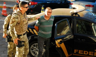 Cesare Battisti é escoltado por policiais federais em Corumbá, no Mato Grosso do Sul Foto: Fabio Marchi/AFP/05-10-2017