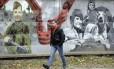 Lembrança seletiva. Russo passa por mural que retrata heróis da Segunda Guerra na cidade de Volkhov: Kremlin prefere valorizar o conflito em que derrotou a Alemanha nazista, e não a Revolução Russa, que foi uma contestação ao poder Foto: Dmitri Lovetsky / AP/2-10-2017
