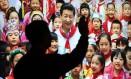 Chinês acena em frente a imagem do presidente Xi Jinping rodeado de crianças em Pequim Foto: Andy Wong / AP