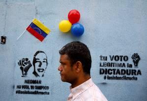 """Homem caminha em frente a graffiti onde se lê """"Seu voto legitima a ditadura"""", em Caracas Foto: Carlos Garcia Rawlins / REUTERS"""