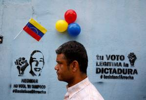 Homem caminha em frente a grafite que diz