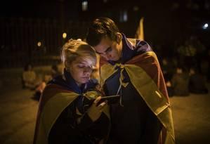 Reunidos em Barcelona, apoiadores da secessão catalã acompanham no celular debate no Parlamento local Foto: SANTI PALACIOS / AP