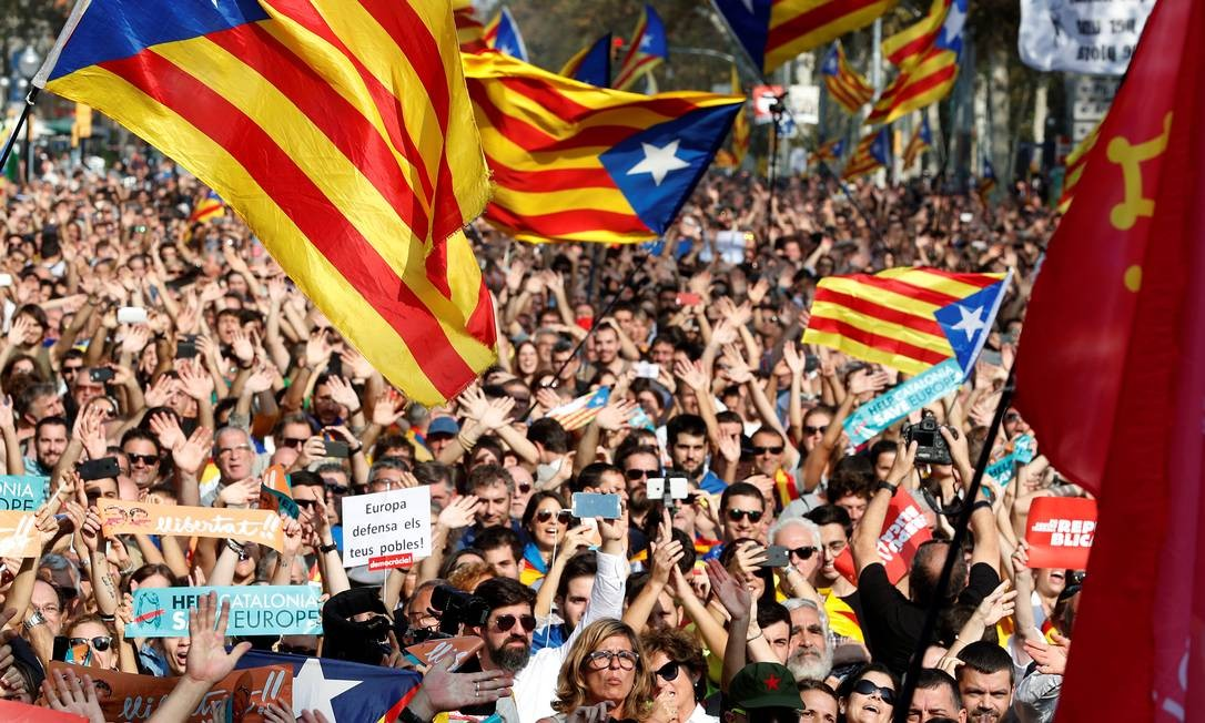 Com Esteladas, bandeiras independentistas catalãs, manifestantes assistem à contagem dos votos no Parlamento local sobre separação em telão Foto: YVES HERMAN / REUTERS
