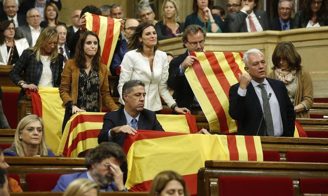 Oposição catalã, que é contra a separação, levou bandeiras espanholas à sessão do Plenário antes do voto sobre a independência Foto: Manu Fernandez / AP